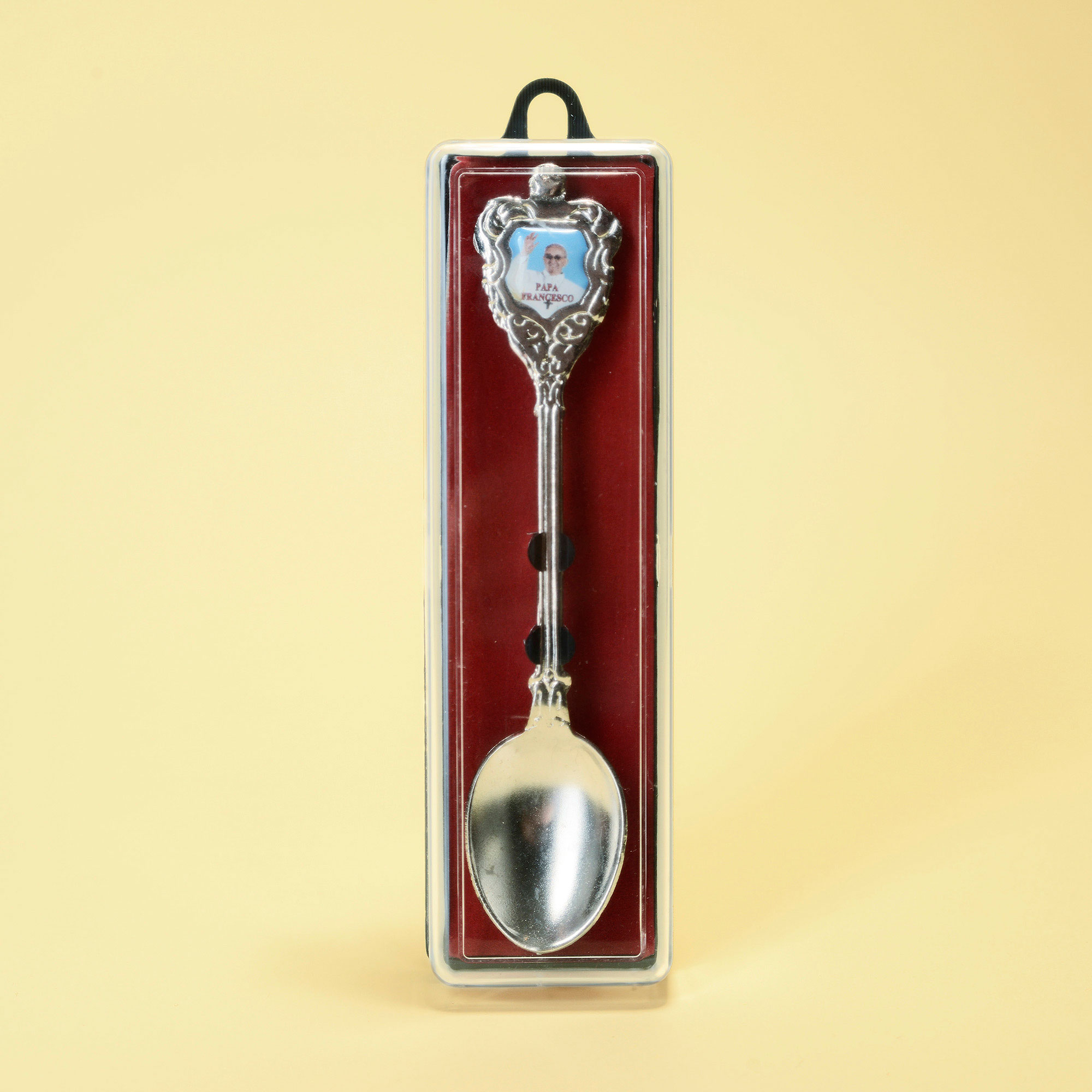Metal spoon with little photograph of Pope Francis in plastic box.