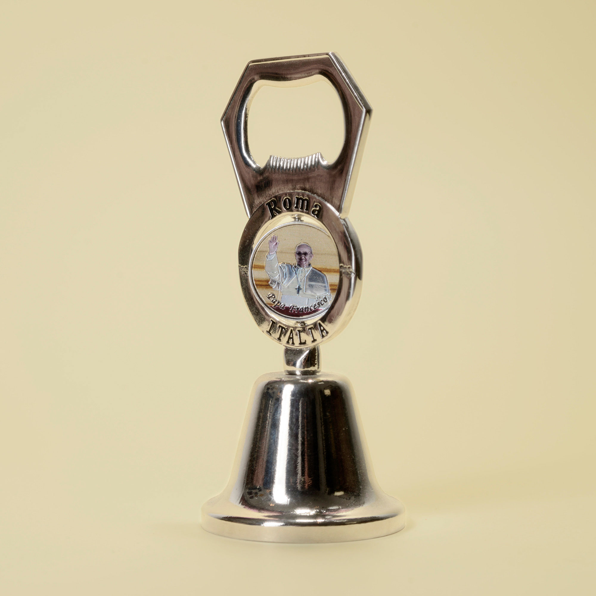 Metal bell and bottle opener with turning image of Pope Francis (on the other side Pope John Paul II).